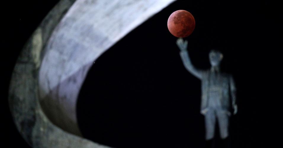 15.abr.2014 - Lua cheia em eclipse é registrada junto do monumento a Juscelino Kubitschek, em Brasília. O eclipse lunar total desta terça-feira durou, entre todas as fases, mais de três horas, desde quando a lua começa a se mover para a sombra da Terra. Pouco mais de uma hora depois, a lua foi vista totalmente eclipsada e envolta em um tom vermelho, justificando o apelido de 'lua de sangue'
