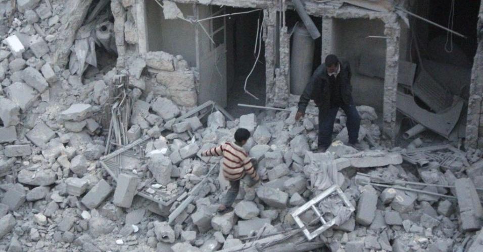15.abr.2014 - Um homem ajuda um garoto a se deslocar entre escombros em um local atingido pela explosão de um barril-bomba que, segundo ativistas, foi detonado por forças leais ao ditador Bashar al-Assad, no bairro de al-Ansari, em Aleppo (Síria), nesta terça-feira (15)