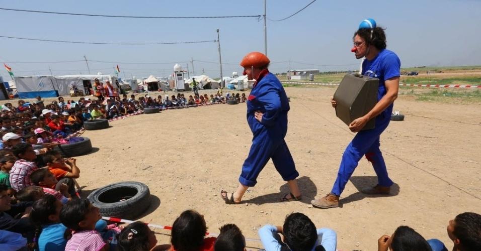 19.abr.2014 - Palhaços divertem crianças sírias do campo de refugiados Quru Gusik, no Curdistão iraquiano, neste sábado (19). A Síria destruiu cerca de 80% de seu material de armas químicas declaradas, segundo informações da agência Reuters