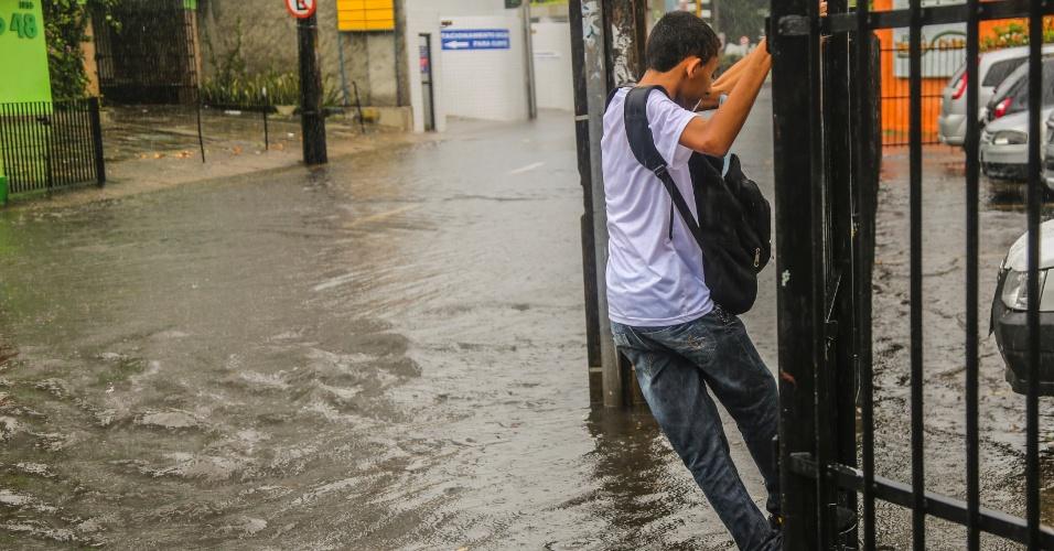 22.abr.2014 - A forte chuva que atinge o Recife (PE) desde o início desta terça-feira (22) provoca alagamentos em diversos pontos da cidade, deixando o trânsito congestionado em várias regiões. Nesta foto, um jovem tenta desviar de trecho cheio d'água