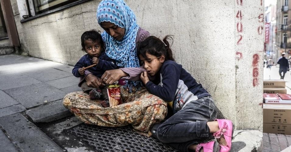 22.abr.2014 - Mulher de origem síria senta-se em uma calçada em Istambul (Turquia), com os dois filhos, nesta terça-feira (22). O número de refugiados sírios recebidos pelo país chegou a quase um milhão, de acordo com informações do primeiro-ministro Recep Tayyip Erdogan, que se comprometeu a continuar aceitando aqueles que fogem da guerra civil que assola a Síria há mais de três anos