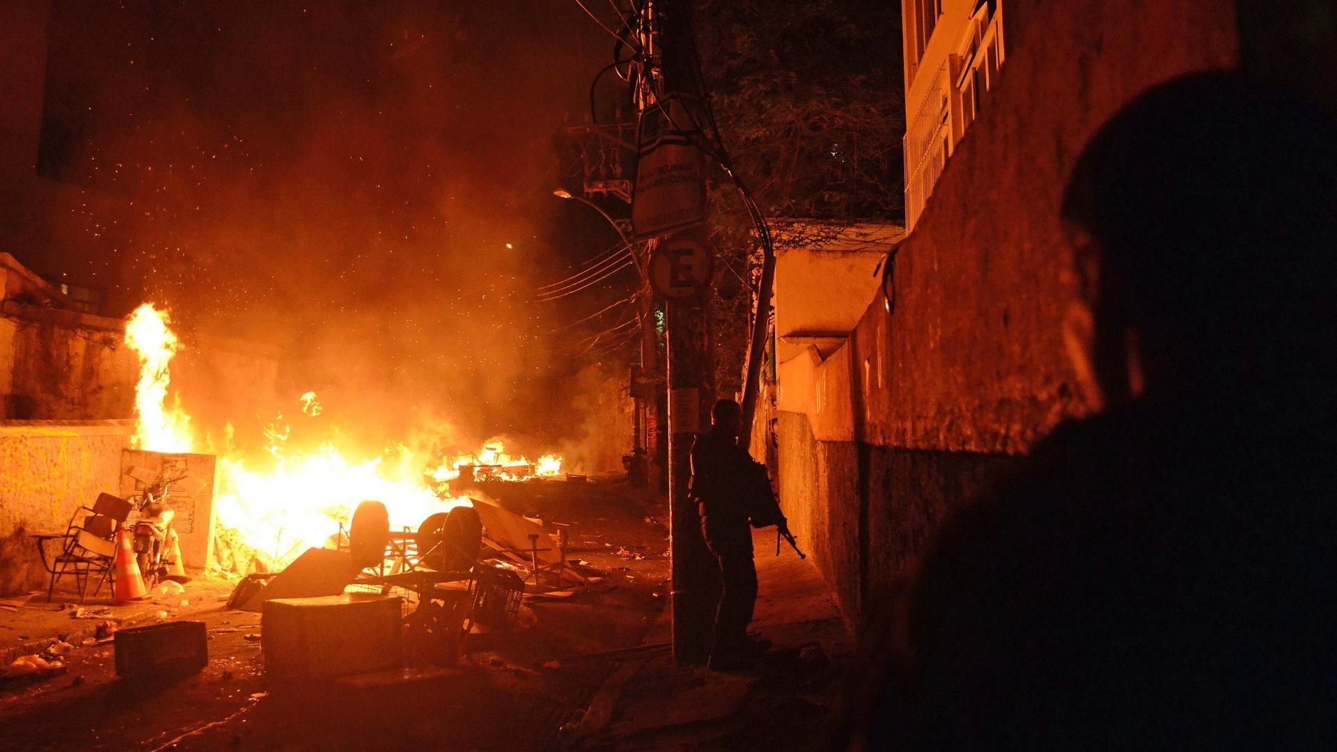 22abr2014---policiais-tomam-posicao-proximos-a-barricada-em-chamas-incendiada-por-moradores-da-favela-pavao-pavaozinho-em-copacabana-na-zona-sul-do-rio-de-janeiro-nesta-terca-feira-22-em-protesto-1398210905384_1920x1080.jpg