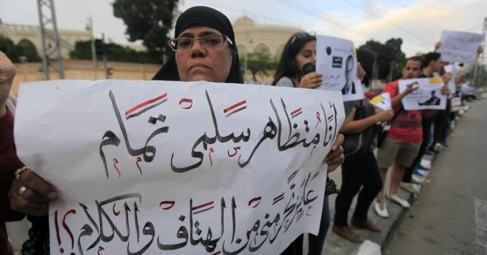 23.abr.2014 - Ativistas protestam contra a lei que restringe os protestos e para pedir a libertação de manifestantes detidos em frente ao edifício presidencial no Cairo, Egito, nesta quarta-feira (23). O cartaz diz: