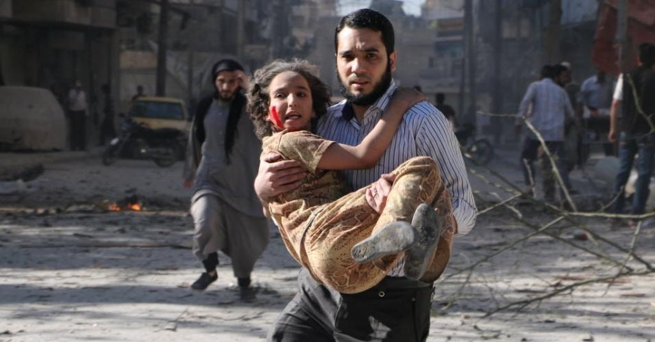 27.abr.2014 - Homem carrega uma menina ferida em ataque com barris explosivos lançados pelo governo sírio em Aleppo, neste domingo (27)