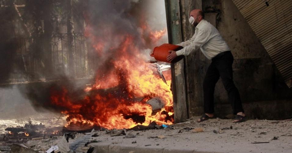 27.abr.2014 - Homem tenta apagar incêndio causado por ataque com barris explosivos lançados por forças leais ao presidente Bashr Al-Assad, em Aleppo, neste domingo (27)