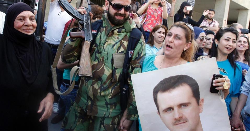 28.abr.2014 - Apoiadores do presidente sírio, Bashar al-Assad, comemoram o anúncio de que ele vai concorrer à reeleição para um terceiro mandato nas eleições de junho no país, nesta segunda-feira (28). Assad submeteu formalmente sua candidatura à corte constitucional da Síria