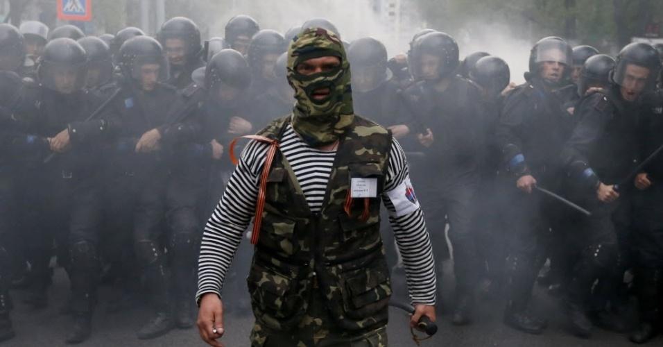 28.abr.2014 - Ativista pró-Rússia caminha em frente a policiais durante protesto a favor dos ucranianos em Donetsk, cidade no leste da Ucrânia, região que tem sofrido intervenção de separatistas. Os Estados Unidos congelaram ativos e impuseram novas sanções contra 17 empresas e sete funcionários do governo da Rússia, nesta segunda-feira (28), em decorrência da não retirada dos grupos separatistas da Ucrânia e da influência russa nas ações desses grupos