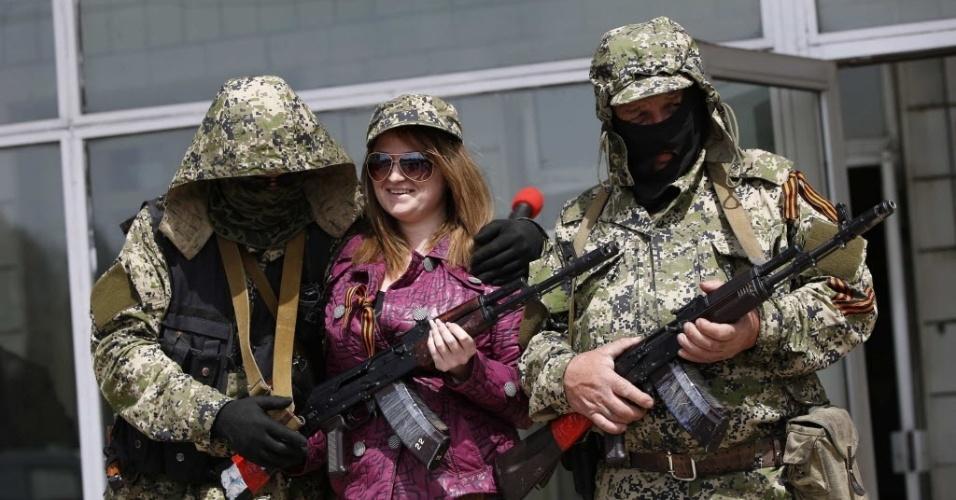 28.abr.2014 - Mulher posa para foto ao lado de mascarados armados pró-Rússia na sede da Prefeitura de Kostyantynivka, no leste da Ucrânia, que foi tomada por separatistas nesta segunda-feira (28). O grupo também assumiu o controle do QG da polícia, segundo informações de um porta-voz do governo local
