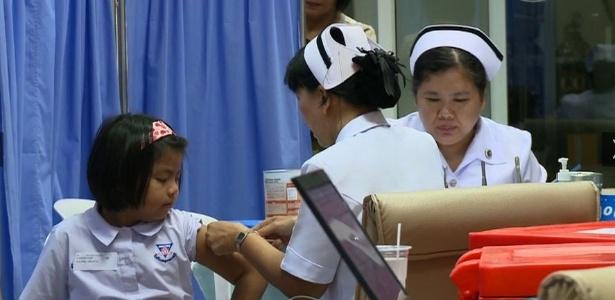 Criança recebe vacina contra dengue na Tailândia, em estudo de fase 3 conduzido pela Sanofi Pasteur desde 2011. Esta outra vacina também está em testes no Brasil