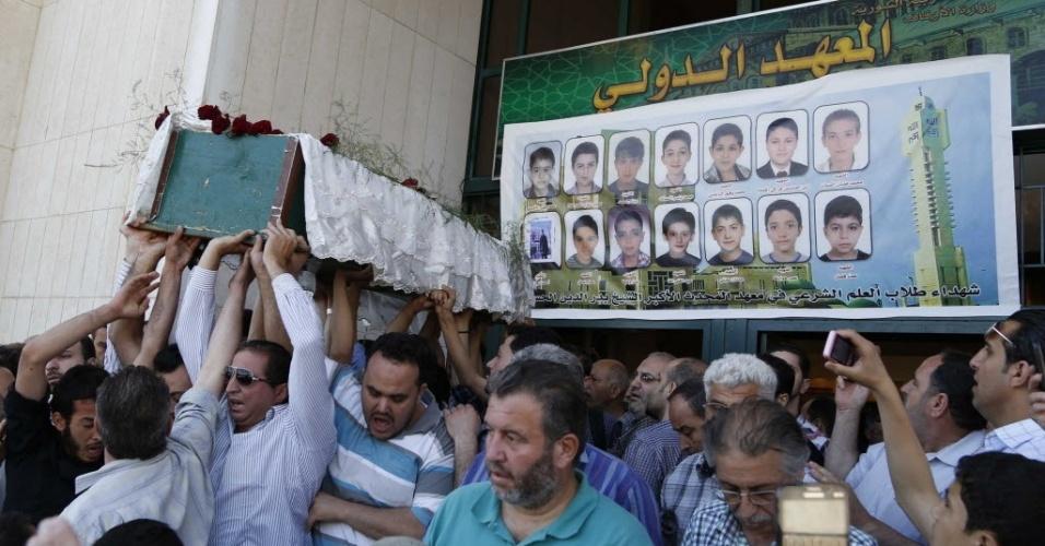 30.abr.2014 - Sírios carregam caixão durante funeral, nesta quarta-feira (30), de uma das vítimas dos ataques feitos com morteiros ao distrito xiita de Shagour, na região central de Damasco (Síria), nesta terça-feira (29). Ao menos 51 pessoas morreram quando carros-bomba explodiram e morteiros foram lançados no local e também na cidade de Homs, um dia após o presidente Bashar al-Assad anunciar que vai concorrer à reeleição em junho. Nos últimos três anos de conflitos civis, 100 mil pessoas morreram no país, de acordo com organizações humanitárias