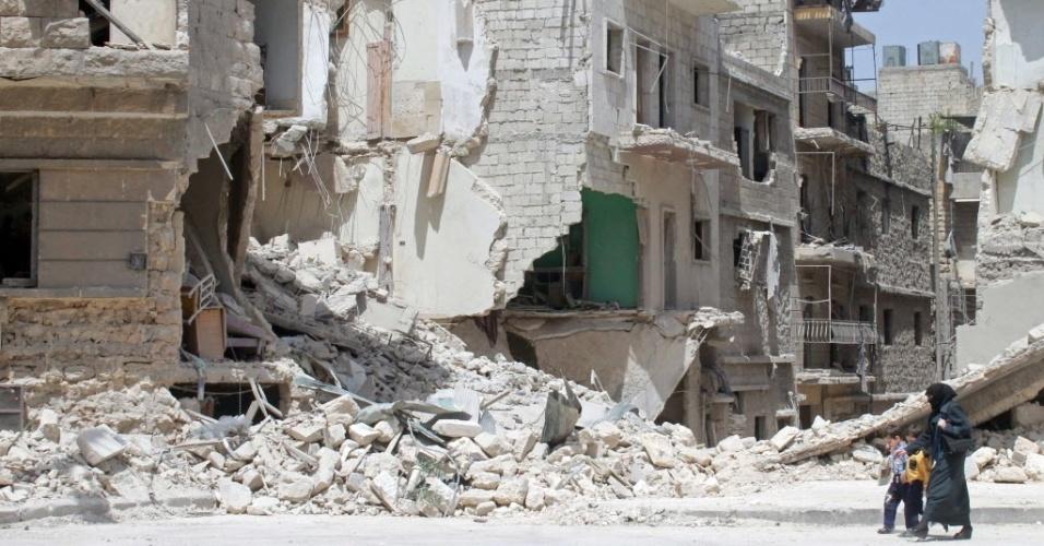 7.mai.2014 - Mulher síria caminha com duas crianças em frente a prédios destruídos no norte da cidade de Aleppo. Esta semana o governo retomou o controle de partes de Homs que estavam sob o controle de grupos rebeldes