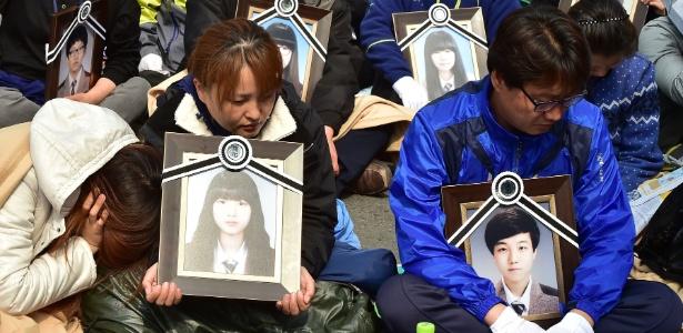 Pais seguram retratos de seus filhos que morreram no naufrágio da balsa Sewol durante protesto