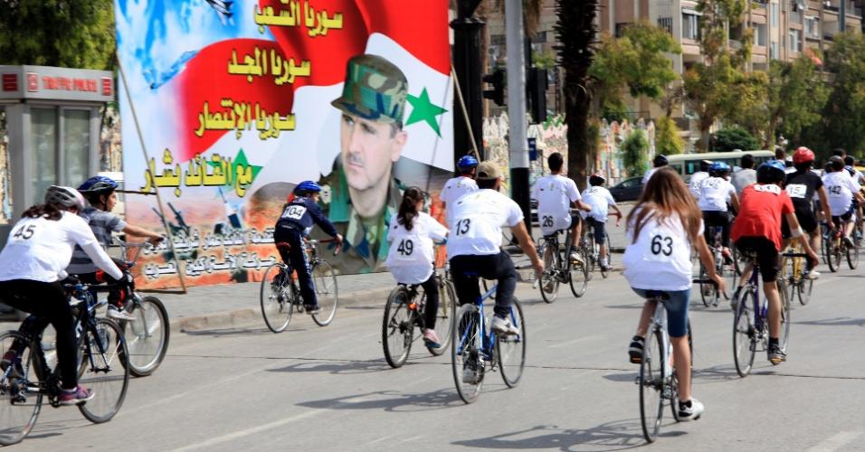 9.mai.2014 - Ciclistas participam do evento 'A Síria Pulsa com Vida', diante de cartaz com o rosto do ditador Bashar Al-Assad, em Damasco