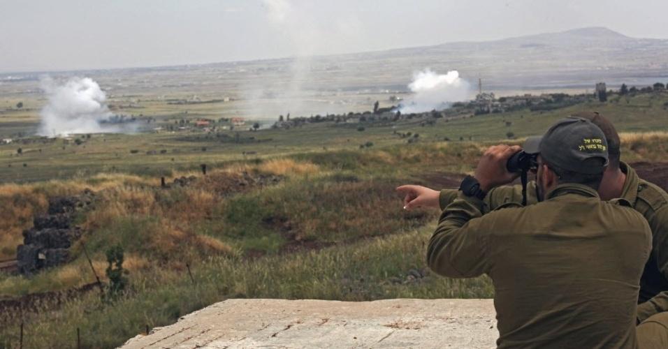 9.mai.2014 - Soldados israelenses observam fumaça de bombardeio de forças governamentais da Síria no povoado de Qahtaniya, que fica na fronteira com Israel e foi capturado por rebeldes sírios. Os rebeldes anunciaram em redes sociais o início de operações militares para controlar a região na fronteira entre os dois países