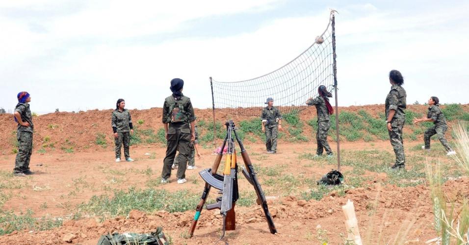 12.mai.2014 - Milicianas curdas da Unidade de Proteção Feminina jogam vôlei em campo de treinamento próximo a Qamishli, na Síria. A imagem, de domingo (11), foi divulgada nesta segunda