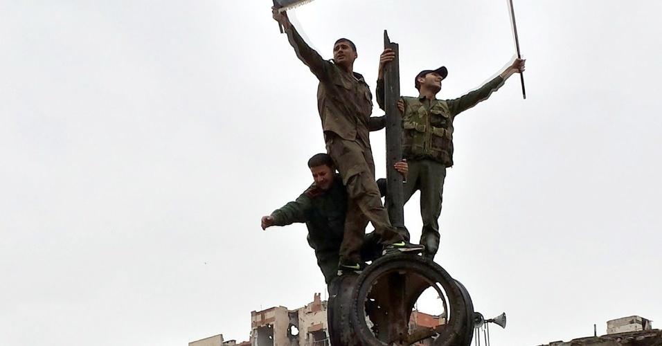 12.mai.2014 - Soldados exibem bandeira nacional da Síria e retrato do presidente Bashar Assad na cidade de Homs, destruída pela guerra civil no país, que já dura três anos