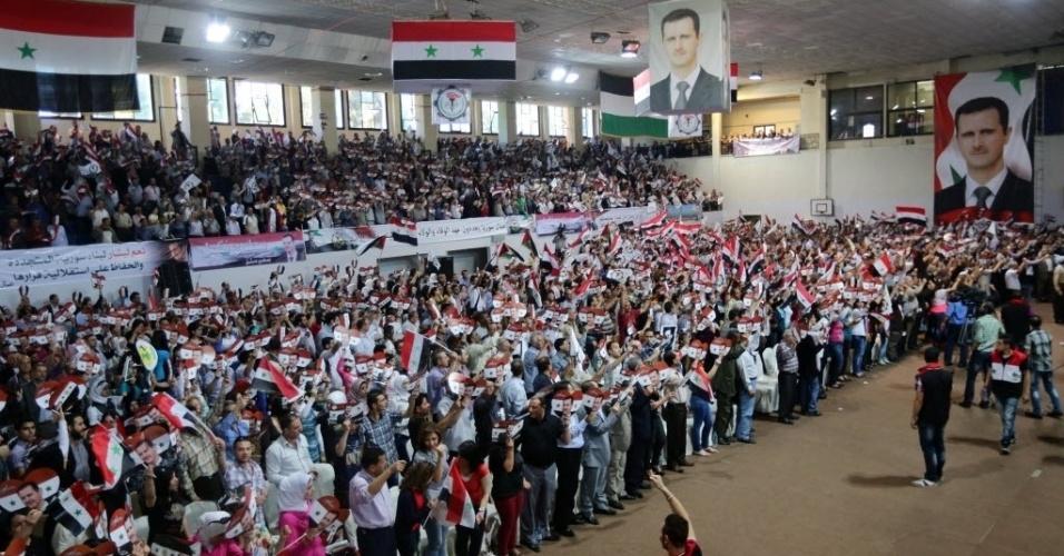 13.mai.2014 - Sírios seguram bandeiras e cartazes em formato de coração com fotografias do ditador Bashar al-Assad, durante uma reunião para apoiá-lo nas próximas eleições, em Damasco, capital do país