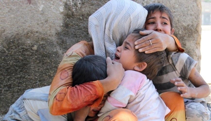 14.mai.2014 - Uma mulher síria conforta seus filhos após a sua casa na vizinhança de Sahour, norte de Aleppo ser bombardeada. O ministro das Relações Exteriores da França, Laurent Fabius, afirmou na terça-feira (13) que a Síria utilizou armas químicas em
