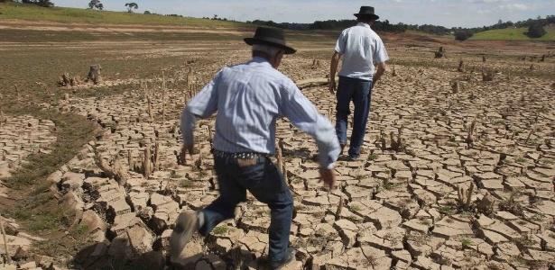15.mai.2014 - Homens caminham pelo leito seco de um dos reservatórios do sistema Cantareira