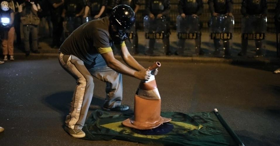 15.mai.2014 - Manifestante coloca cone sobre bandeira do Brasil, enquanto é observado por policiais militares, durante protesto contra a Copa do Mundo no Rio de Janeiro, nesta quinta-feira (15)