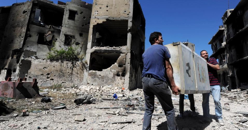 16.mai.2014 - Sírios carregam geladeira de volta para casa, em Homs, nesta sexta-feira (16). As forças leais ao ditador Bashar al-Assad expulsaram os rebeldes da cidade, e muitos moradores estão voltando para seus lares