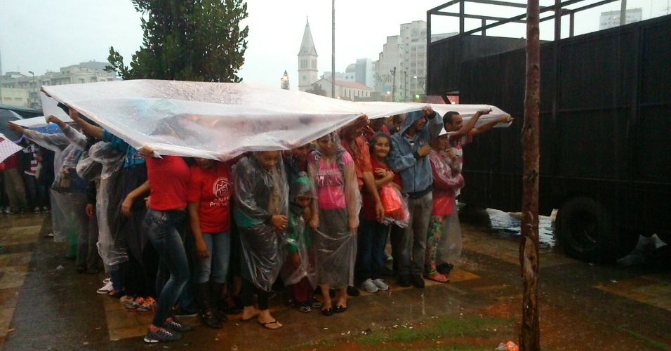 22.mai.2014 - Manifestantes que se concentram no largo da Batata, em Pinheiros, zona oeste de São Paulo, se abrigam da chuva na tarde desta quinta-feira (22). Sem-teto, estudantes, e integrantes de outros movimentos sociais contrários à Copa do Mundo se reúnem no local em um protesto que tem como objetivo