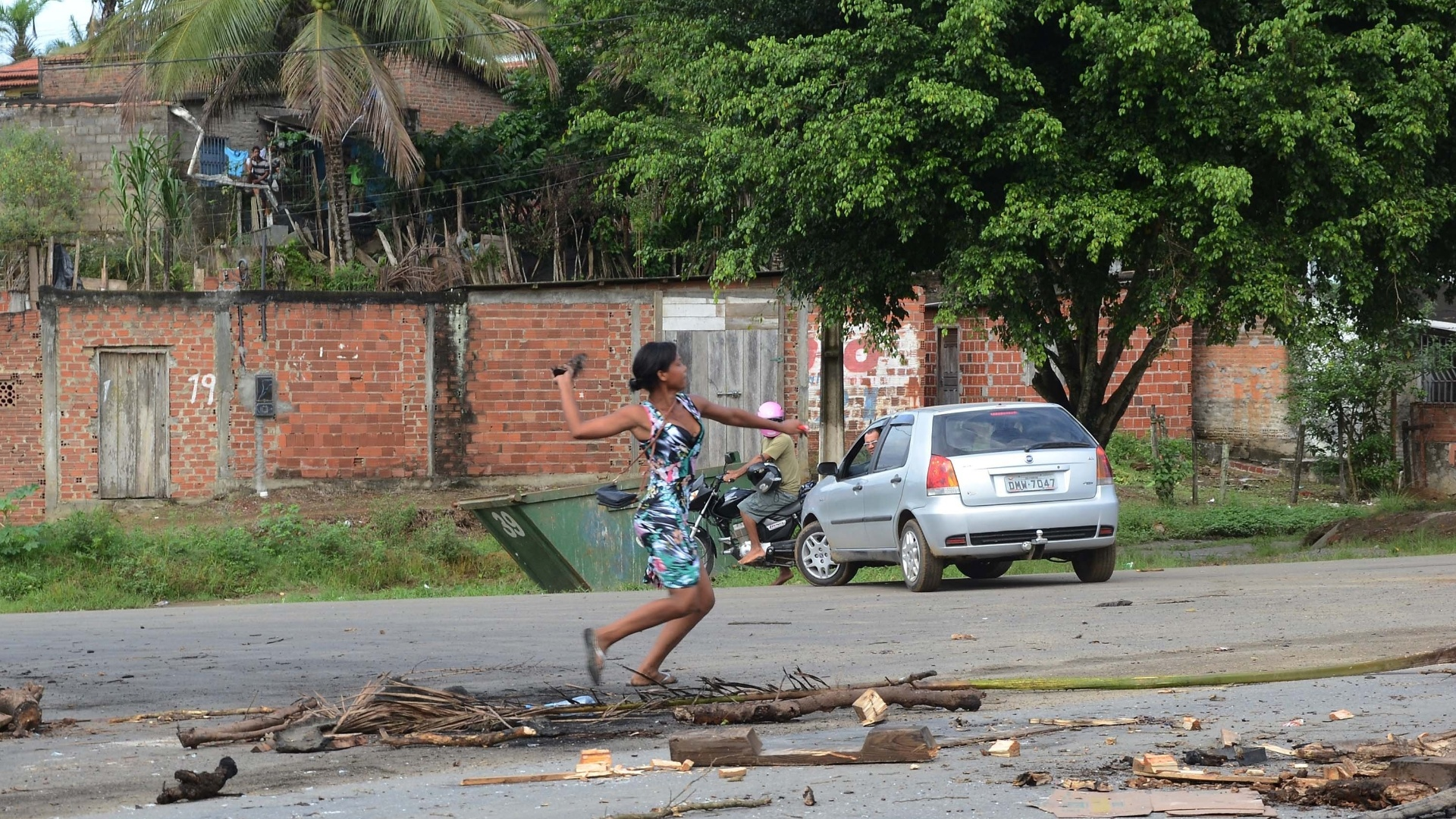 23.mai.2014 - Parente de preso lança objeto durante protesto em que a rodovia BR-415 foi bloqueada em Itabuna, na Bahia, nesta sexta-feira (23). Os detentos do presídio de Itabuna se rebelaram. O complexo, que tem capacidade para 430 presos, abriga mais de 1.200. Esta é a terceira rebelião de 2014