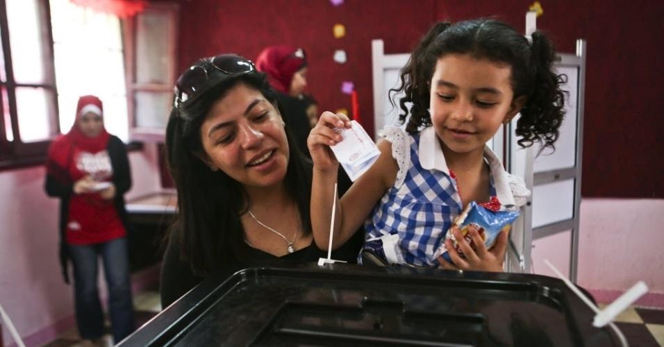 26.mai.2014 - No colo de sua mãe, menina coloca cédula eleitoral em urna durante eleições presidenciais do Egito. Votam nesta segunda e terça-feira 53 milhões de eleitores. Seus resultados serão anunciados no dia 5 de junho e, posteriormente, serão convocadas eleições legislativas