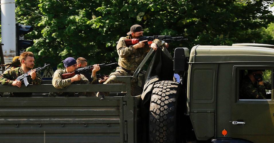 26.mai.2014 - Caminhão com militantes pró-Rússia armados passa por ponto de inspeção policial, a caminho do aeroporto de Donetsk, no leste da Ucrânia, nesta segunda-feira (26). Jornalistas relataram escutar tiros e explosões na vizinhança do aeroporto da cidade, enquanto caças sobrevoavam a região. Um dia após a eleição presidencial no país, rebeldes forçaram o fechamento do aeroporto e assumiram o terminal. Trinta e cinco insurgentes foram mortos em um ataque do exército ucraniano nesta terça (27)