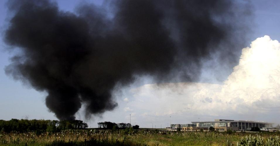 26.mai.2014 - Coluna de fumaça preta se forma no aeroporto internacional de Donetsk, na Ucrânia, durante um tiroteio entre o exército ucraniano e militantes pró-Rússia, na segunda-feira (26). Nesta terça (27), as forças ucranianas conseguiram retomar o controle do aeroporto, com o uso de helicópteros e bombardeios. Segundo o prefeito separatista da cidade, 35 insurgentes morreram em um ataque a bomba