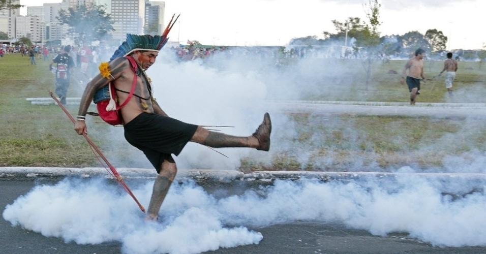 27.mai.2014 - Índio tenta chutar bomba de gás lacrimogêneo lançada por policias, próximo ao estádio Mané Garrincha, em Brasília, durante protesto pela defesa dos direitos territoriais dos povos indígenas garantidos na Constituição. A manifestação, que se juntou ao ato contra a Copa do Mundo no Brasil, busca chamar a atenção sobre a situação da Amazônia