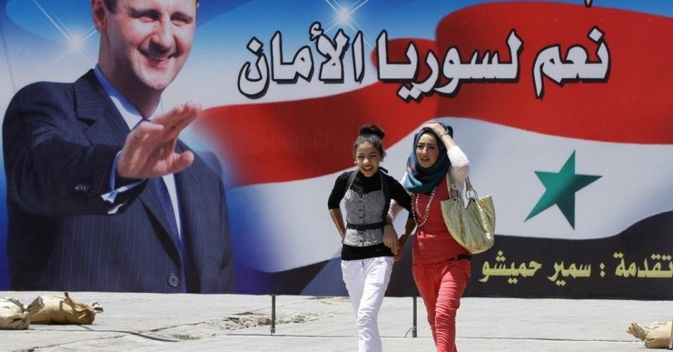 27.mai.2014 - Mulheres sírias passam por outdoor com propaganda da candidatura à reeleição do presidente Bashar Assad em Damasco. Com o slogan