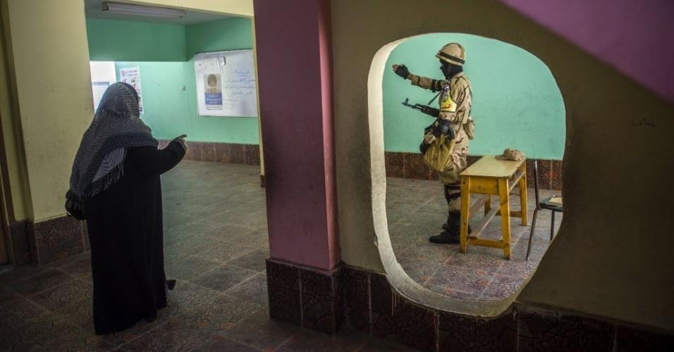 27.mai.2014 - Um soldado egípcio aponta o local de votação a uma mulher no segundo dia de eleição presidencial no país, nesta terça-feira (27). A Comissão Eleitoral Suprema decidiu estender até quarta-feira (28) o processo eleitoral para
