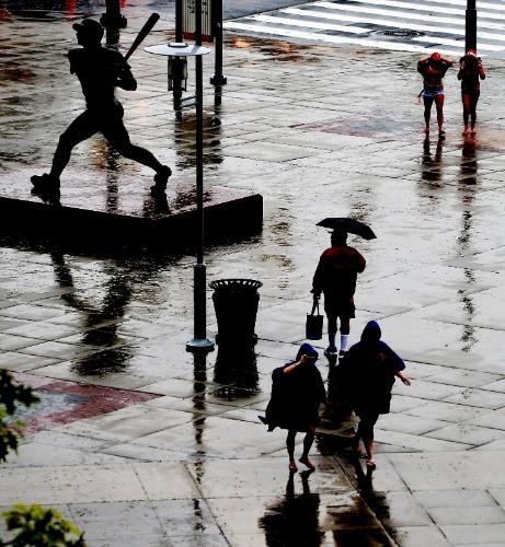 27.mai.2014- Fãs correm na chuvar ao chegar a um jogo entre o Colorado Rockies e os Philadelphia Phillies no Citizens Bank Park, na Filadélfia, Pensilvânia, nesta terça-feira (27)