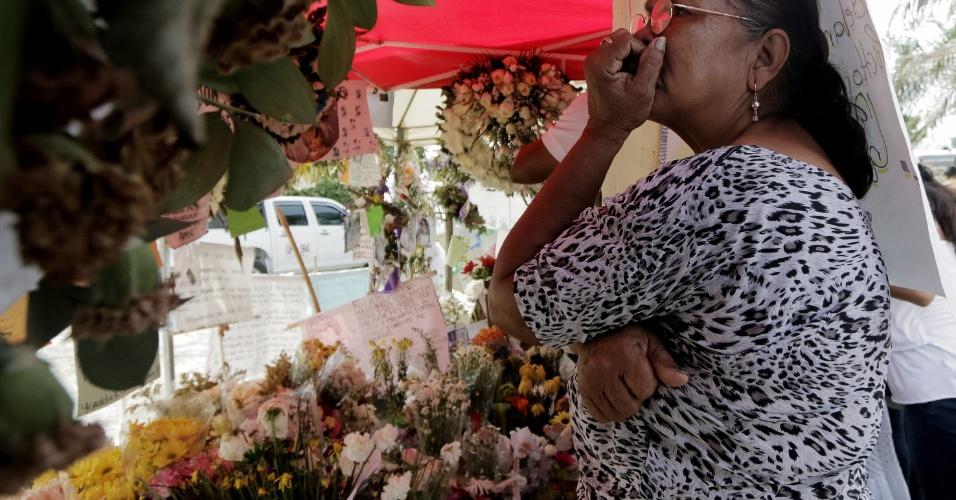 27.mai.2014 -Mulher se emociona diante de altar erguido no local onde 33 crianças de Fundação (Colômbia) morreram em 18 de maio, após o ônibus que as transportava de um culto religioso de volta a suas casas pegou fogo. Amanhã (28), será realizado o enterro coletivo das crianças