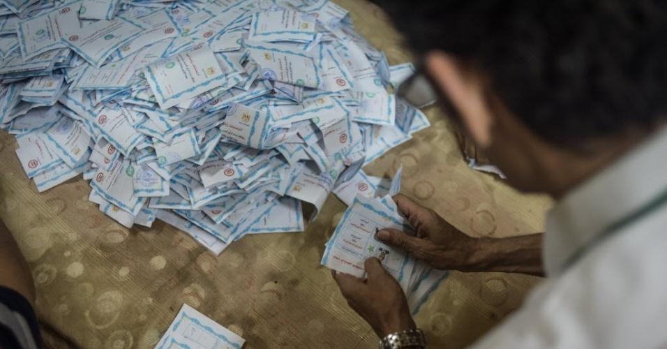 28.mai.2014 - Trabalhador eleitoral egípcio organizar cédulas após o horário de encerramento da votação no Cairo, nesta quarta-feira (28). Resultados parciais da eleição presidencial do Egito apontam que o ex-chefe do Exército do Egito Abdel Fattah al-Sisi está prestes a alcançar uma vitória
