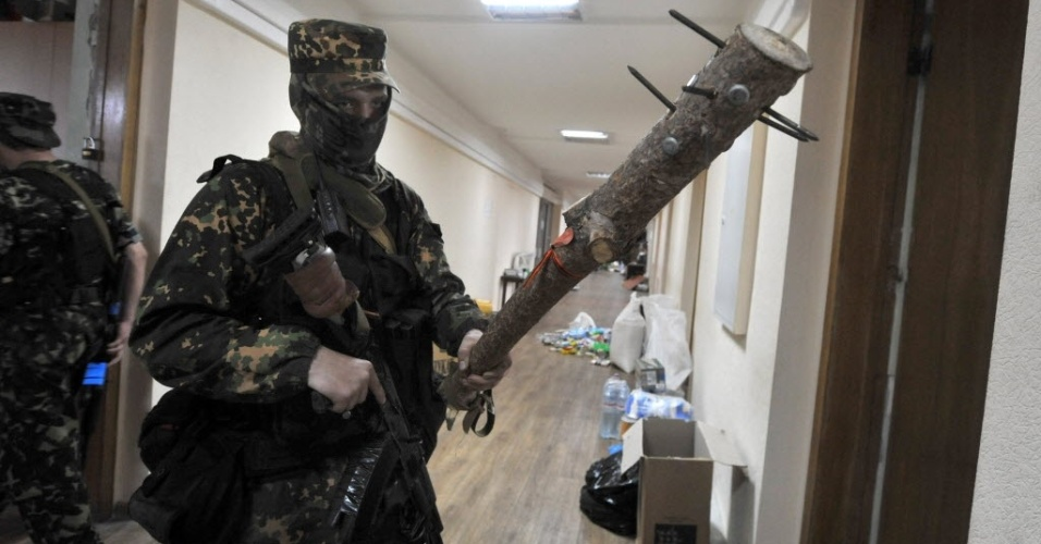 30.mai.2014 - Um rebelde pró-Rússia exibe um porrete cravejado com pregos dentro de um prédio público na cidade ucraniana de Donetsk, nesta quinta-feira (29). Milicianos armados do batalhão Pro-Rússia Vostok cercaram o prédio, exigiram que ativistas da chamada República Popular de Donetsk deixassem o local e prenderam vários deles. Nos últimos cinco dias, cerca de 50 militares ucranianos foram mortos em operações no leste da Ucrânia, palco de conflitos com rebeldes pró-Rússia