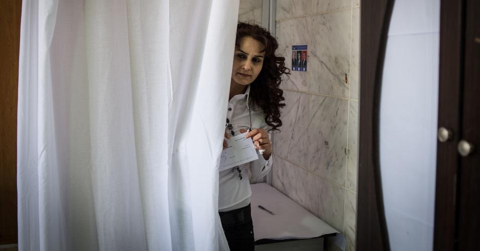 3.jun.2014 - Eleitora deixa local de votação em Homs, na Síria