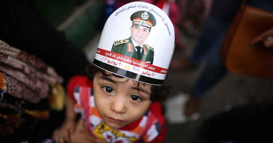 3.jun.2014 - Garoto egípcio usa um chapéu com o retrato do ex-chefe do Exército Abdel Fattah al-Sisi durante celebração da vitória do militar nas eleições presidências do país, na praça Tahrir, nesta terça-feira (3). Ele recebeu com 96,91% dos votos, enquanto o seu único rival, o líder da esquerda Hamdeen Sabbahi, teve apenas 3,09% dos votos. O governo interino instalado por Sisi eliminou da cena política o principal movimento de oposição, o grupo islamita Irmandade Muçulmana