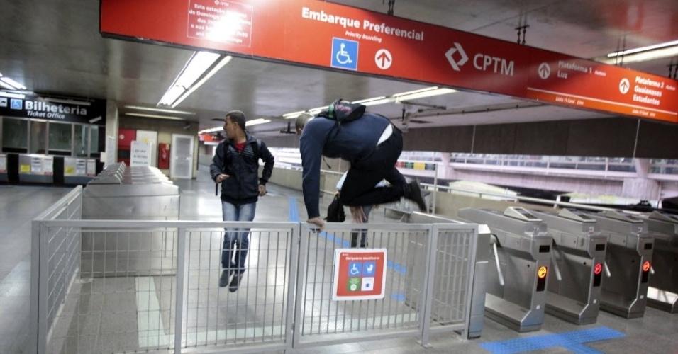 5.jun.2014 - Passageiros saltam sobre o portão de entrada na estação de metrô Itaquera, em São Paulo. O Metrô de São Paulo remanejou funcionários para operar trens e contornar a greve. Com o plano de contingência, as linhas 1, 2 e 3 estão funcionando parcialmente na tarde desta quinta-feira (5)