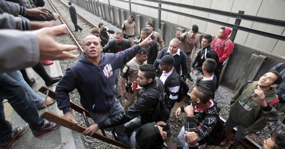 5.jun.2014 - Policiais retiram passageiros dos trilhos, revoltados com a situação do transporte público, devido a greve dos metroviários na estação Corinthians-Itaquera do metrô, na zona leste de São Paulo. Com o plano de contingência, as linhas 1, 2 e 3 estão funcionando parcialmente na tarde desta quinta-feira (5)