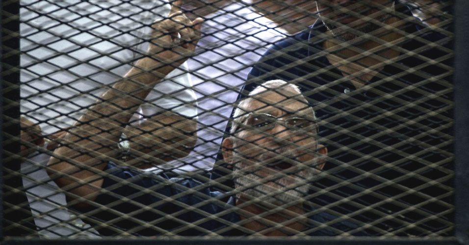 7.jun.2014 - O líder da Irmandade Muçulmana Mohamed Badie faz gesto dentro de uma gaiola onde são colocados os réus em julgamento no Cairo, no Egito, neste sábado (7). Um tribunal egípcio condenou neste sábado à morte dez dirigentes da Irmandade Muçulmana acusados de instigar a violência na província de Qaliubiya, embora as sentenças não sejam definitivas