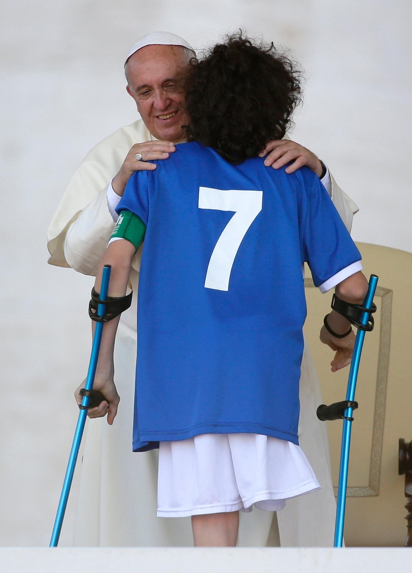 7.jun.2014 - Um membro do time nacional de futebol de amputados da Itália é abraçado pelo papa Francisco durante audiência especial para integrantes do CSI (Centro Italiano de Esportes), na praça de São Pedro, no Vaticano, neste sábado (7)