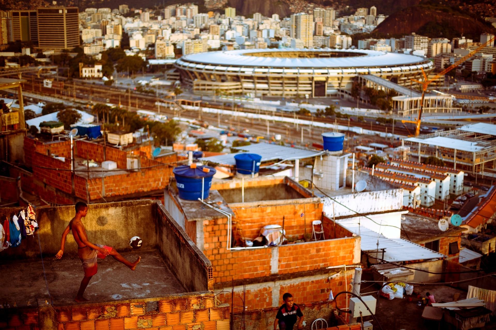 22.mai.2014 - Meninos brincam com uma bola em laje de barraco na favela da Mangueira, no Rio de Janeiro. A cidade carioca e uma das sedes da Copa do Mundo do futebol no Brasil e recebera a final da competicao no estadio jornalista Mario Filho, o Maracana
