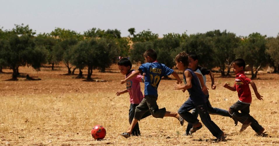 10.jun.2014 - Garotos jogam futebol em um campo em al-Tah onde vivem para pessoas deslocadas, em Idlib, na Síria, nesta terça-feira (10). O local abriga mais de 50 famílias que fugiram da violência dos seus vilarejos