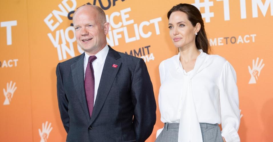 11.jun.2014 - A atriz Angelina Jolie e o ministro das Relações Exteriores do Reino Unido, William Hague, participam de uma cúpula de quatro dias sobre violência sexual em áreas de conflito no Centro de Exposições Excel, em Londres, no Reino Unido, nesta quarta-feira (11)