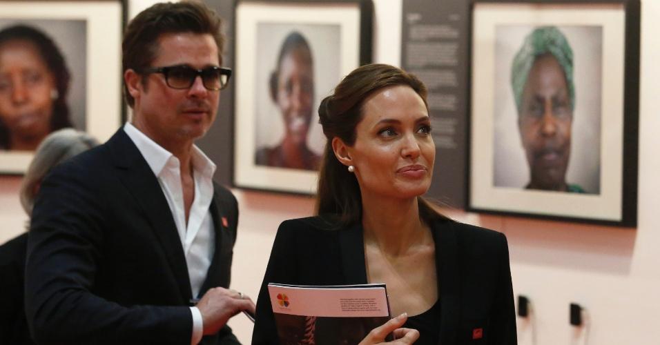 12.jun.2014 - Os atores Angelina Jolie e Brad Pitt observam fotografias em evento à margem da cúpula pelo fim da violência sexual em zonas de conflito no Centro Excel, em Londres, nesta quinta-feira (12)