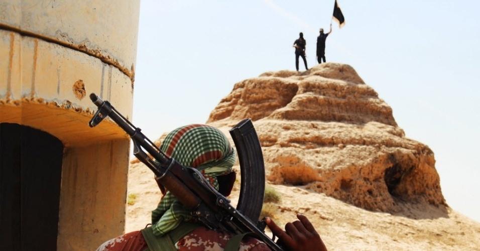 12.jun.2014 - Soldados jihadistas fincam bandeira na província de Salahuddin, no Iraque.Rebeldes sunitas do grupo Estado Islâmico do Iraque e do Levante prometeram tomar Bagdá, depois de invadirem as cidades de Tikrit e Mossul