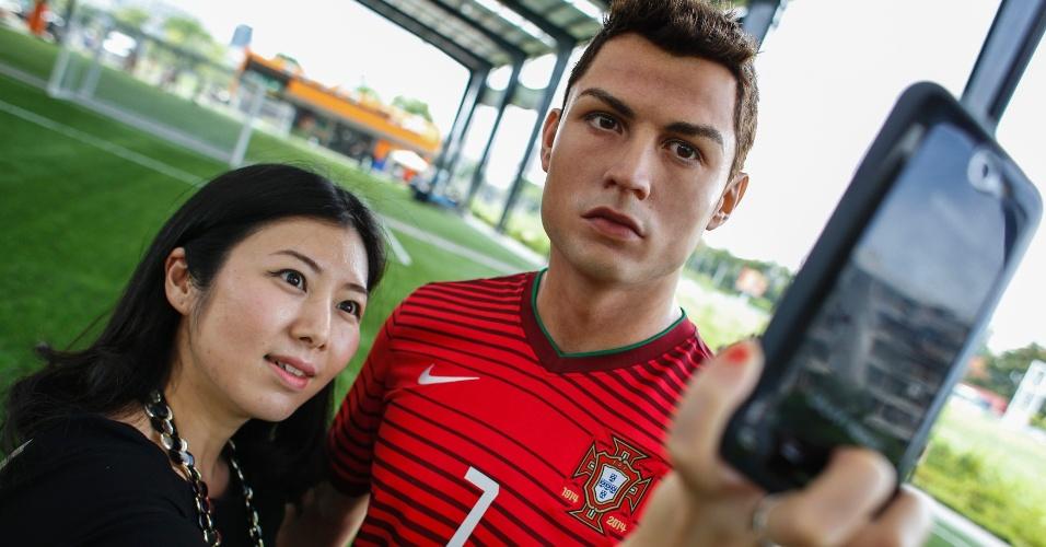 13.jun.2014 - Fã tira uma selfie (autorretrato) ao lado da estátua de cera do jogador português Cristiano Ronaldo durante evento promocional do Museu de Cera Madame Tussaud em Bancoc, Tailândia