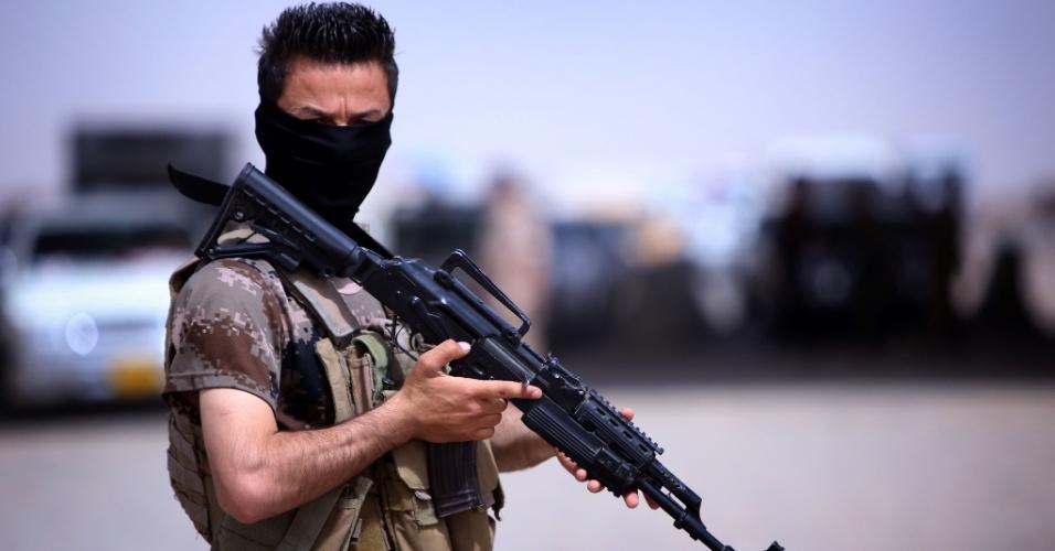 13.jun.2014 - Homem mascarado, da região autônoma curda do Iraque, guarda um acampamento temporário criado para abrigar iraquianos f